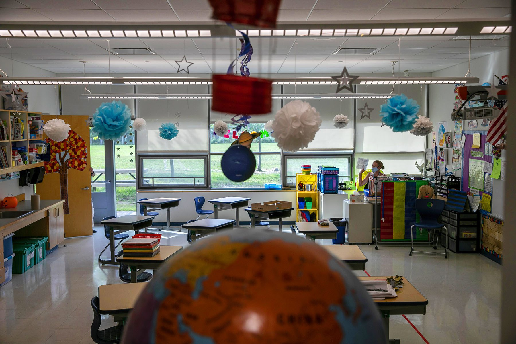 An empty classroom decorated with drawings of planets and trees is seen. A teacher is seen sitting at a desk and wearing a face mask.