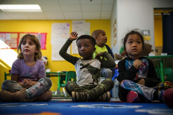 Three small children are seen in a colorful classroom. The child in the middle raises his hand while the other two appear to be listening..