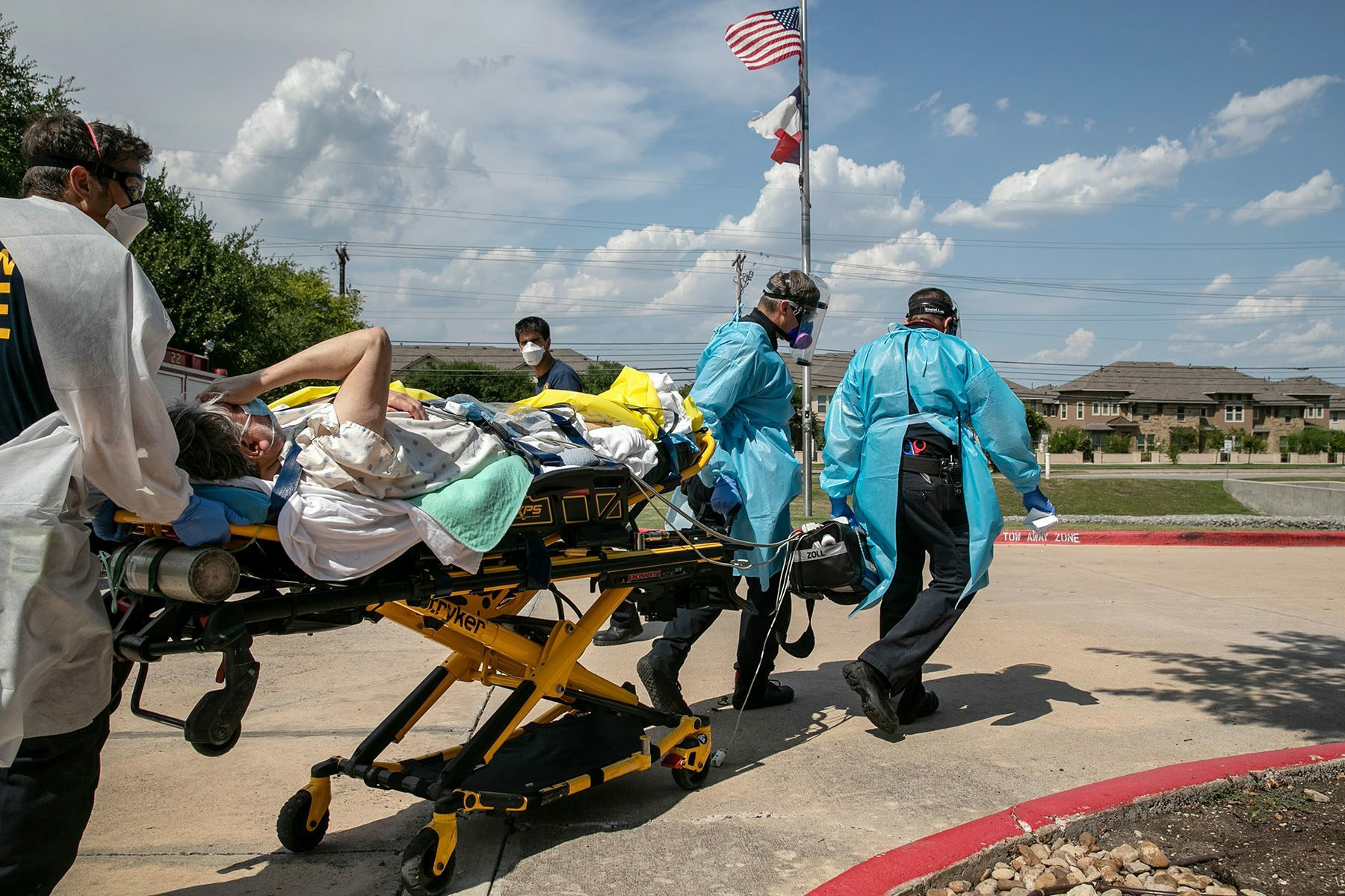 First responders wearing PPE transport a man on a stretcher while he covers his face.