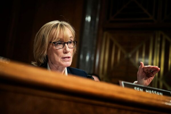 Margaret Hassan is seen at behind a desk while she speaks in Congress.