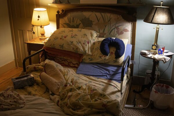 The bedroom of an elderly person is pictured. The bedsheets are undone and on the bed rests a neck pillow and a box of tissue paper that appears empty.