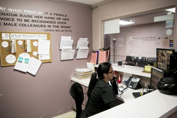 A receptionist is seen answer a phone behind a desk.