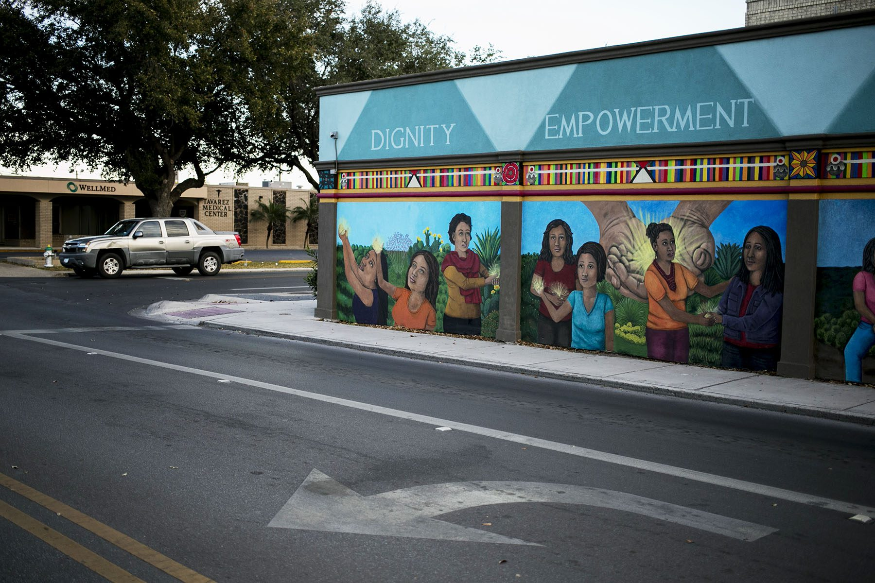 A mural painted on the side of the clinic has the words 'dignity,' 'empowerment,' 'compassion,' and 'justice' accompanying a painted scene where women hold hands and comfort each other.