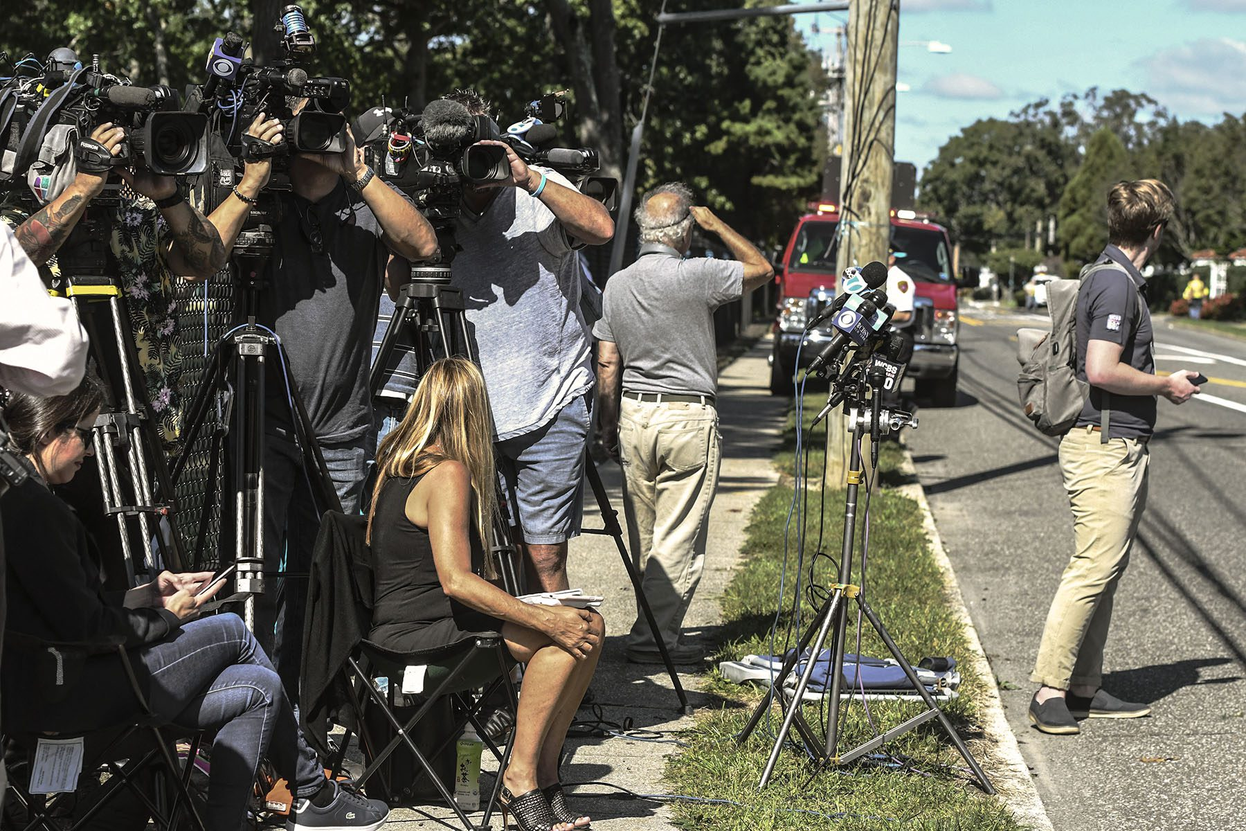 dozens of cameras and microphones, and press are seen on the side of a street.