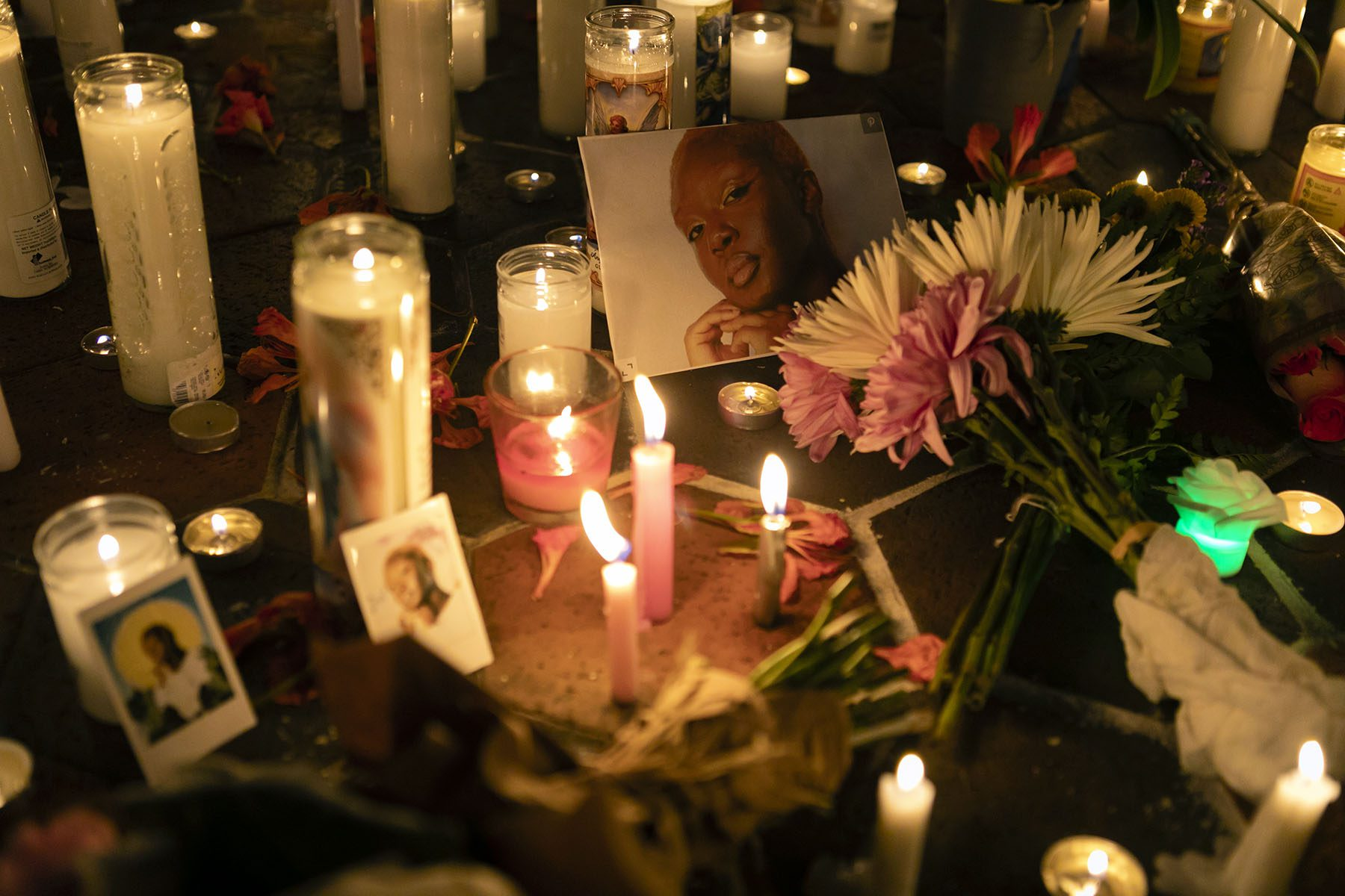 Flowers, lit candles and images of Toyin Salau are laid around the ground during a vigil.