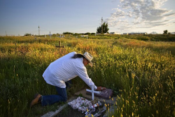 A man wearing a cowboy hat kneels to touch a tomstone in a field at golden hour.