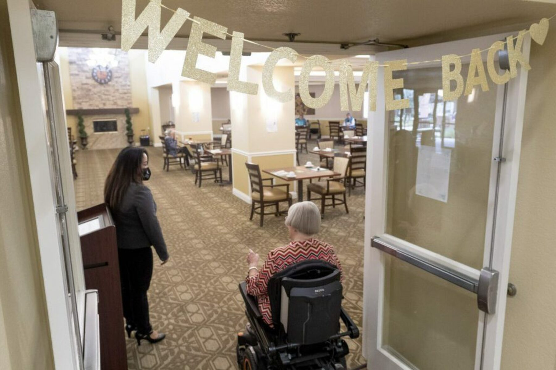 A woman enters the dining room of a nursing home