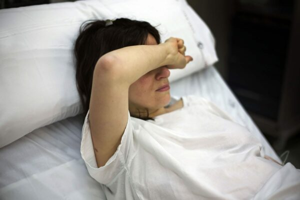 A pregnant woman covers her face while lying in a hospital bed.