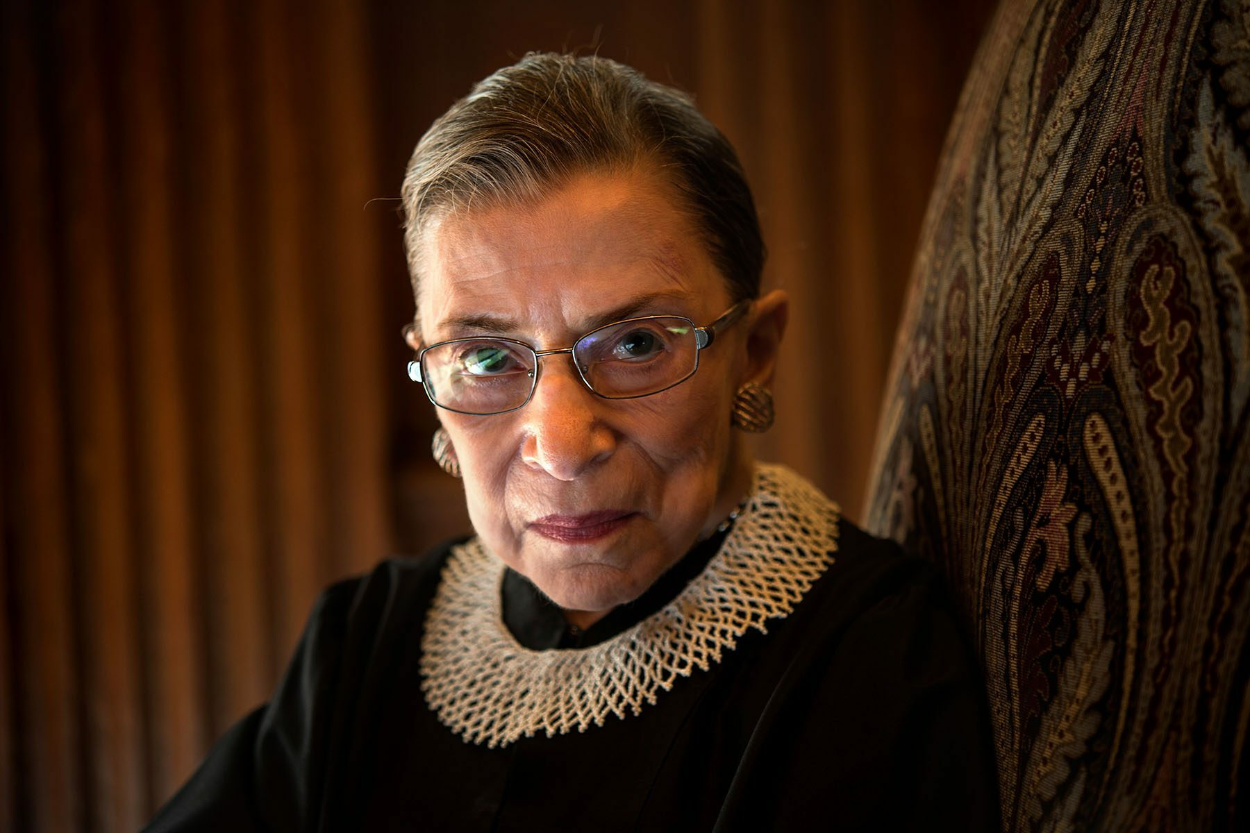 Ruth Bader Ginsburg sits in a chair and looks into the camera.