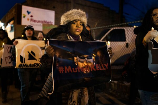 A black woman holds a sign with a picture of R. Kelly with the word #MuteRKelly printed over his face during a demonstration in support of the singer's victims.