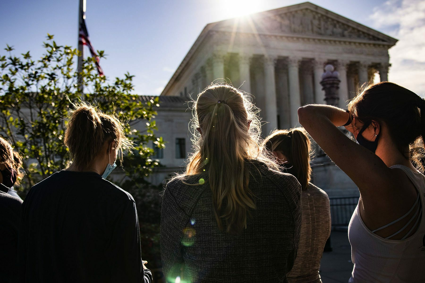 Women wearing masks stand near the U.S. Supreme Court