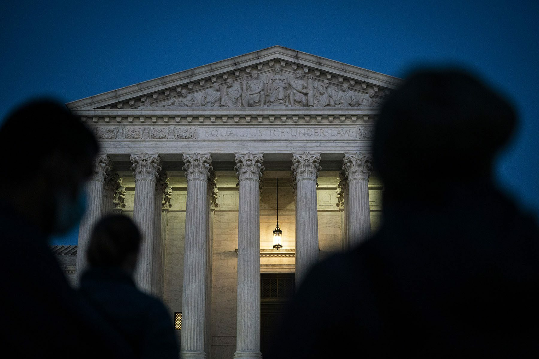 Shadowy figures are seem standing in front of the U.S. Supreme court.