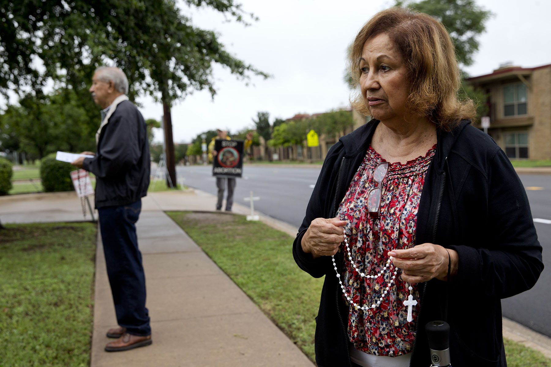 A woman holding a rosary prays outside an abortion clinic.