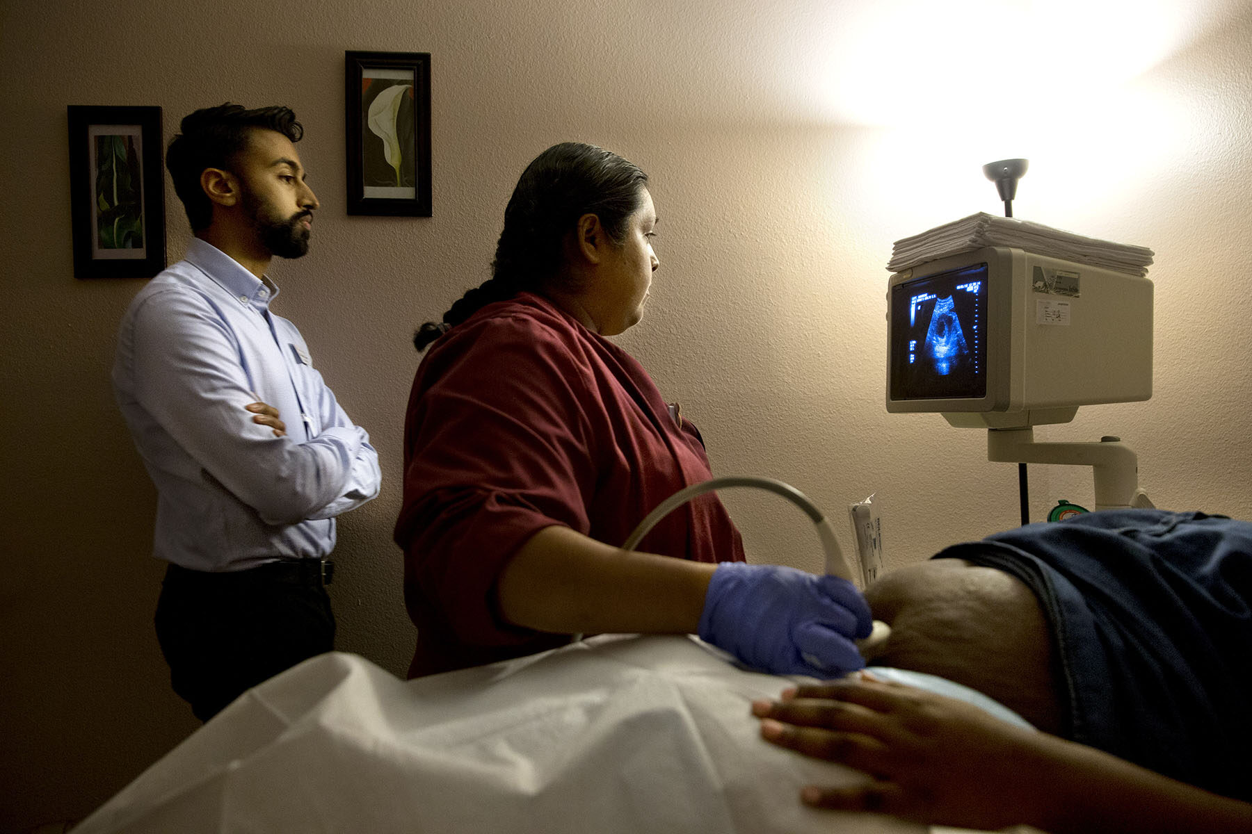 A doctor and a sonographer perform a sonogram on a pregnant patient inside an examination room.