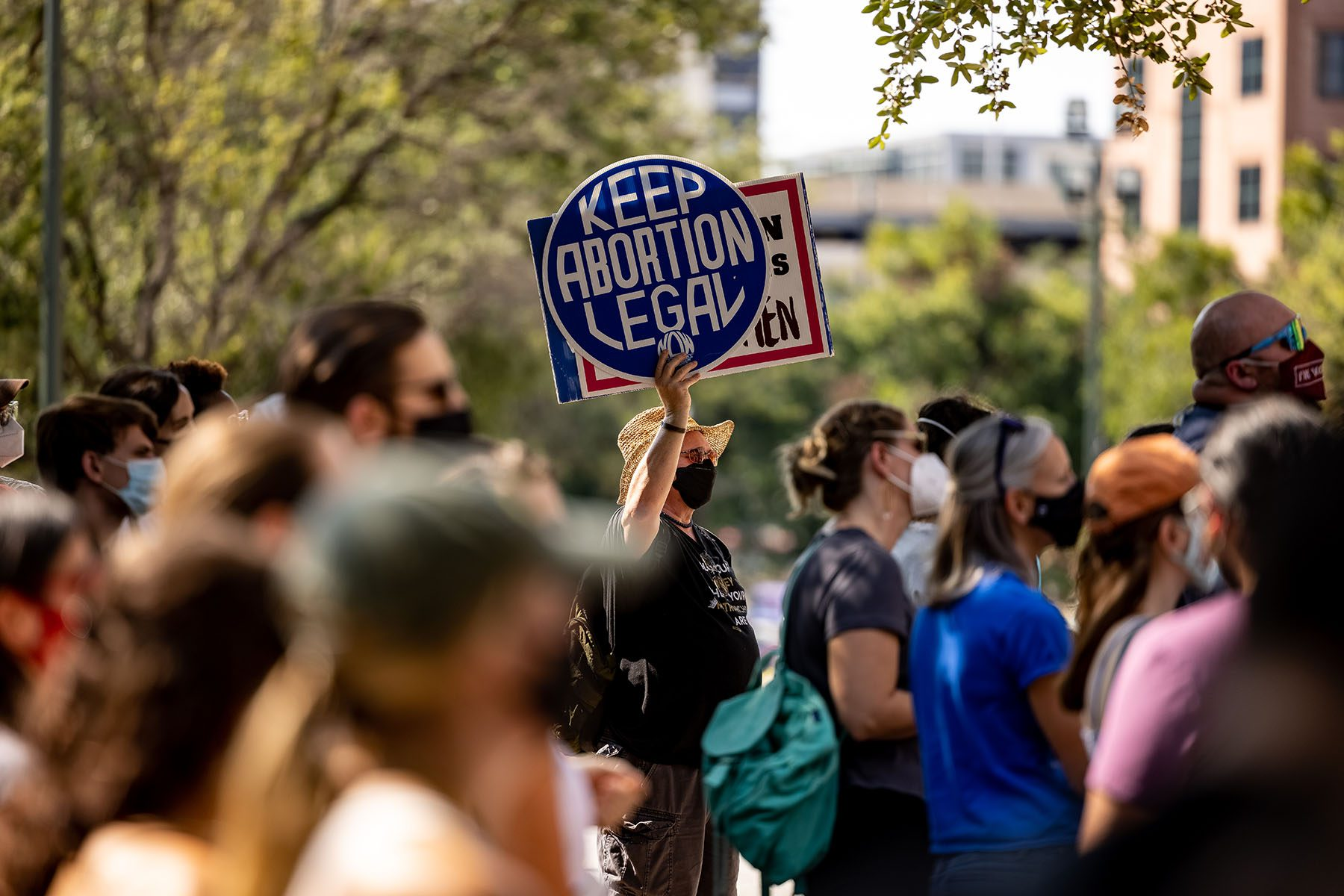 """A person wearing a sat holds up a sign that reads """"Keep Abortion Legal"""" as people gather near the State Capitol to protest the new abortion bill."""