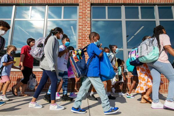 Young students wearing face masks prepare to enter their elementary school on the first day of classes.