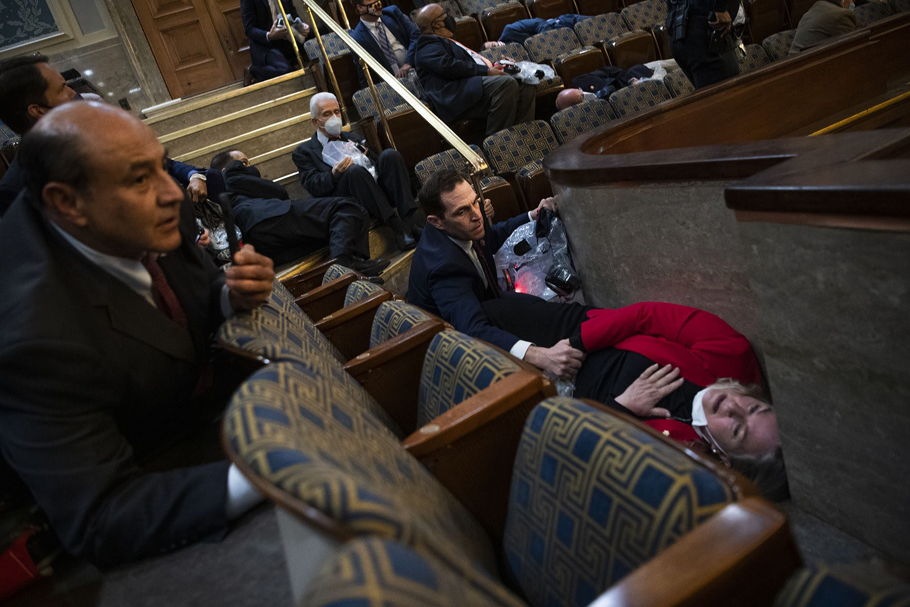 Rep. Susan Wild lays on the floor holding her hand over her heart while Rep. Jason Crow holds her hand to comfort her.