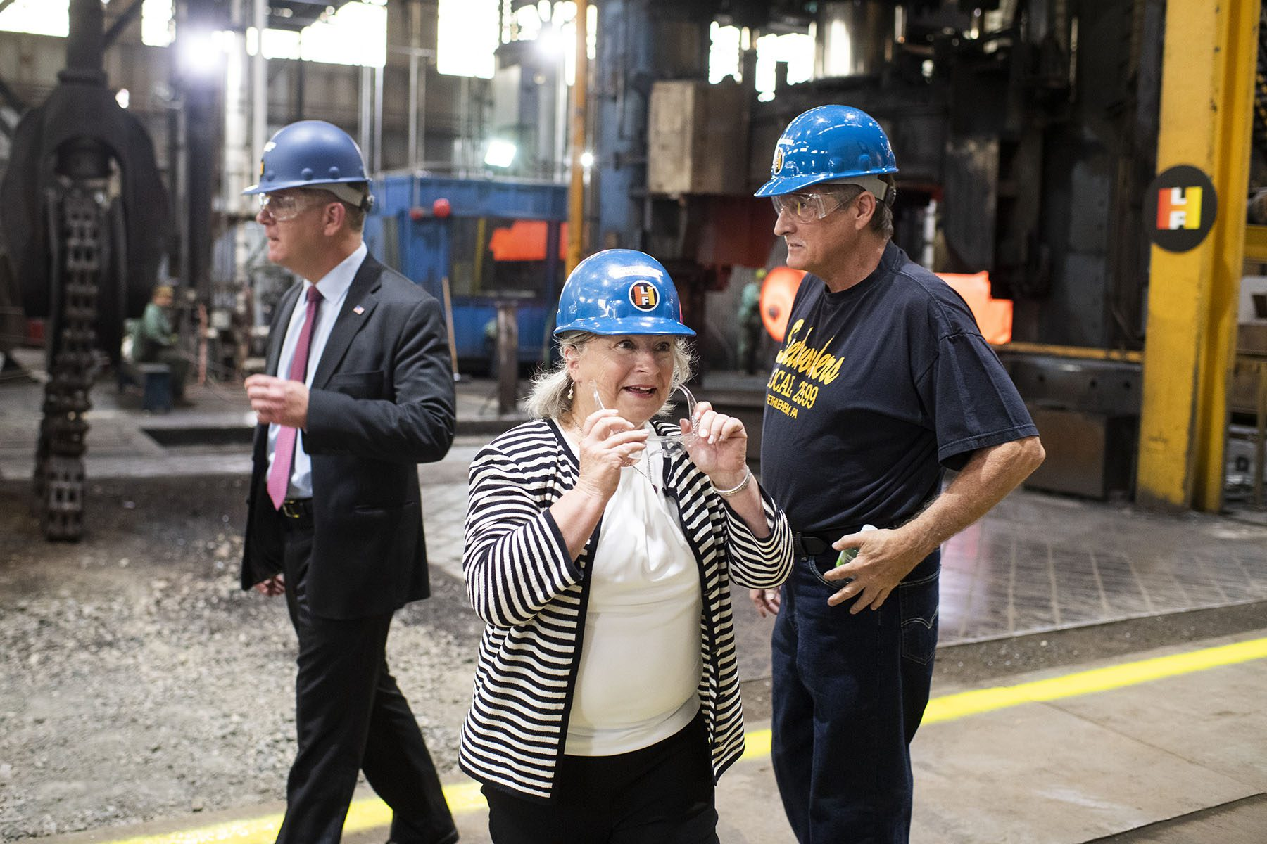 Rep. Susan Wild wears a hard hat and protective glasses while visiting a forge.