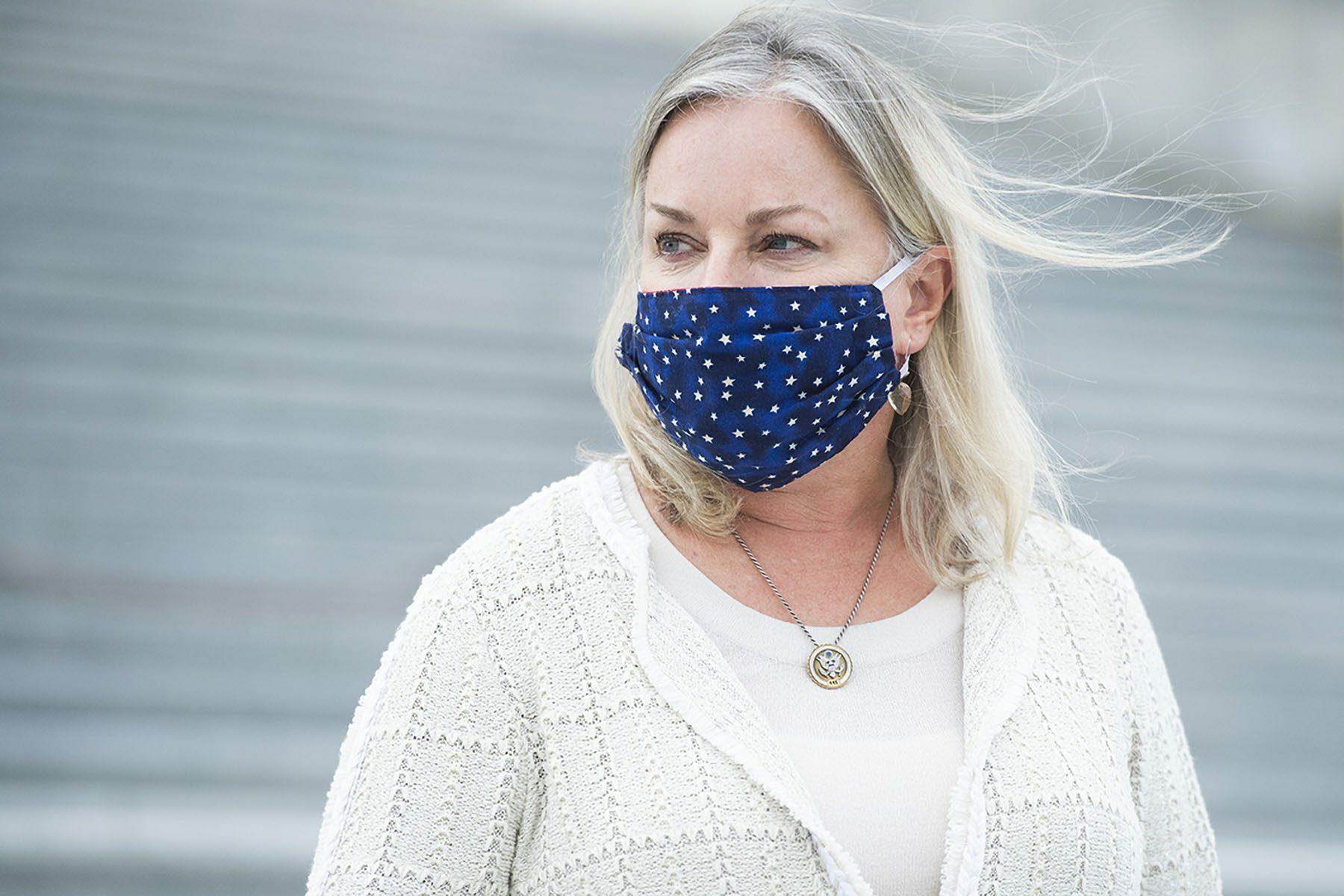 Susan Wild, wearing a blue face masks, stands on the steps on the U.S. Capitol.
