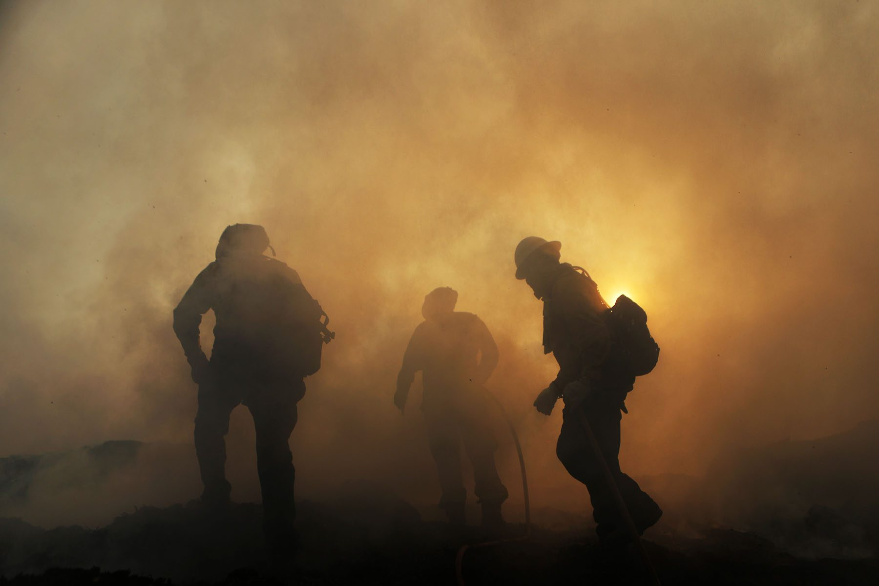 Three firefighters are seen enveloped in thick plumes of smoke.