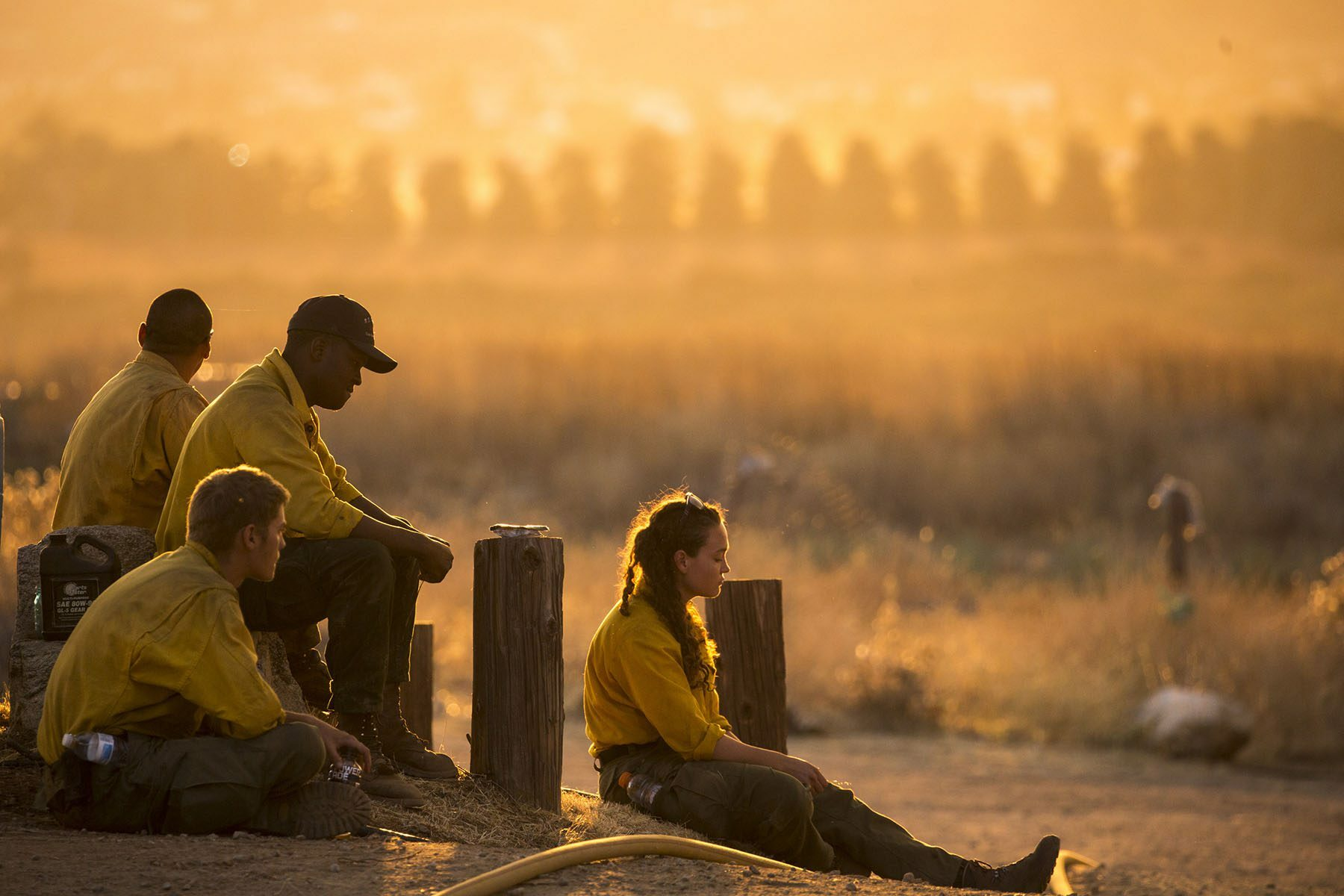 Three male firefighters and one female sit on the ground as golden light and smoke is seen in the distance.