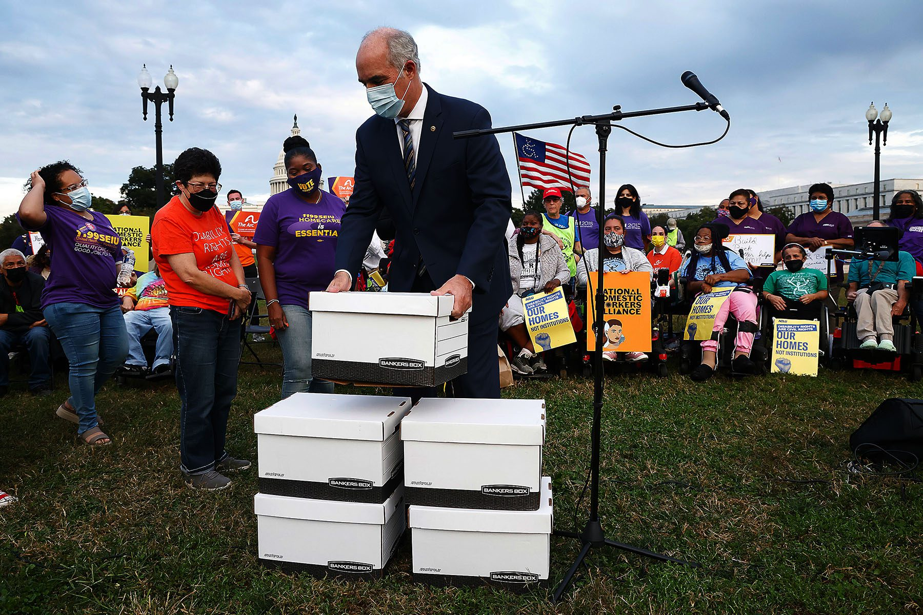 Bob Casey lifts a large white cardboard box while activists watch all around him. The Capitol building is seen in the background.