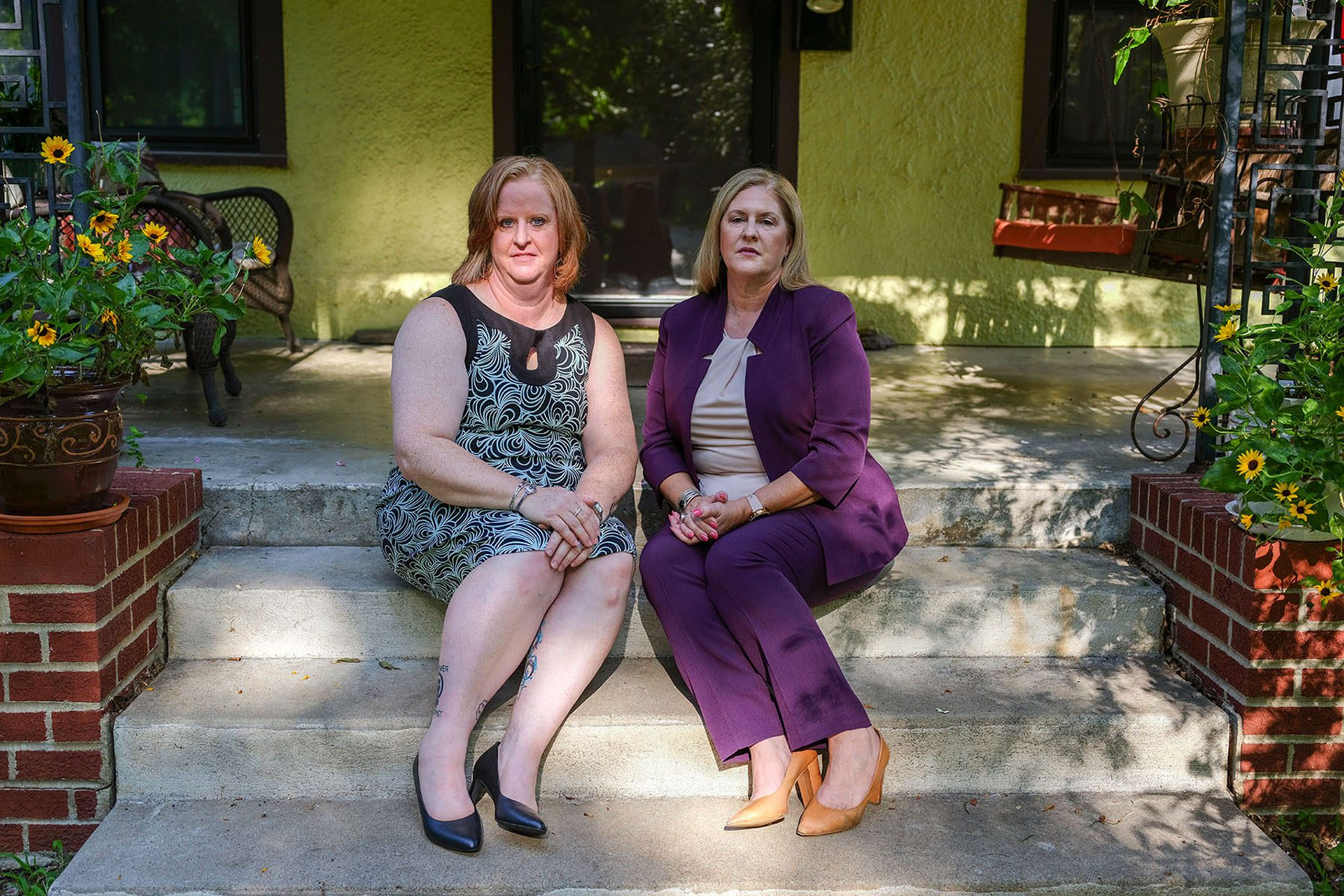 Christie and Julie Burkart pose for a portrait sitting on the stairs of Julie's front porch.