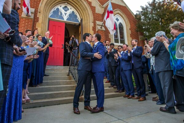 Pete Buttigieg and Chasten Glezman kiss in front of a cathedral while wedding-goers smile and clap.