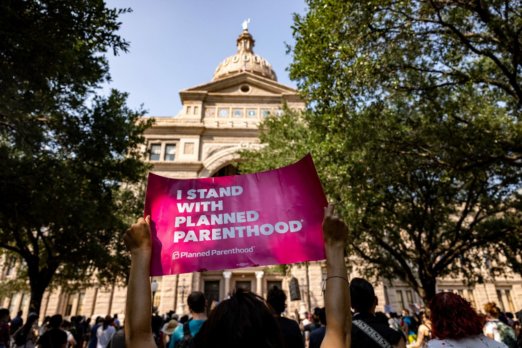 An abortion rights activist holds a sign in support of Planned Parenthood at a rally at the Texas State Capitol.