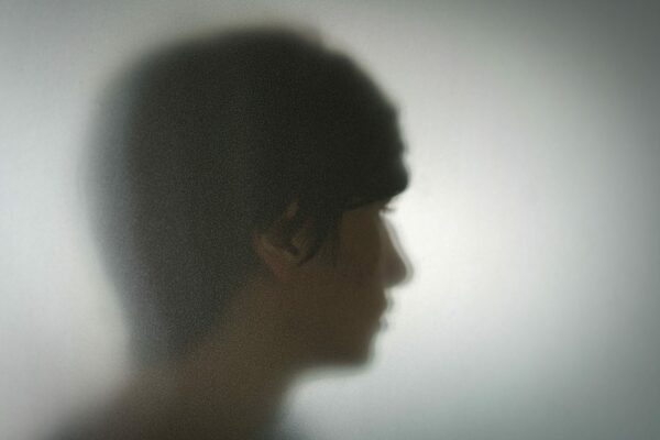 A young person's face is seen, blurred by the pane of glass they are standing behind.