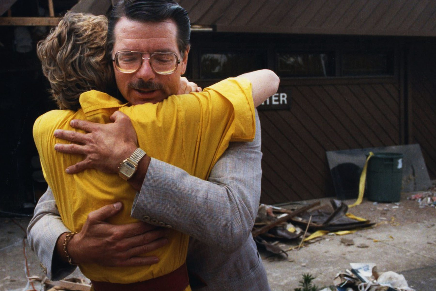 Dr. George Tiller hugs a woman. Behind him are piles of wood and trash from the bombing.