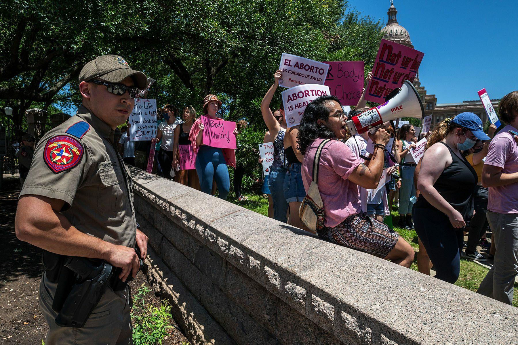 A capitol policeman surveils demonstrators.
