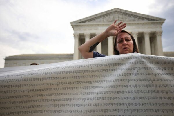 A protester waves her arm into the sky and closes her eyes while holding a large banner in front of the U.S. Supreme Court.