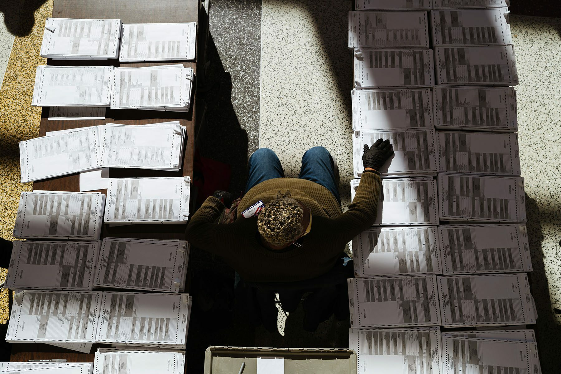 A man sits between two tables on which a laid stacks of blank ballots.