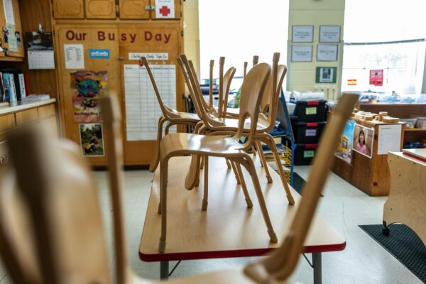 Wooden chairs are stacked on top of tables inside a classroom at the Chambliss Center for Children.