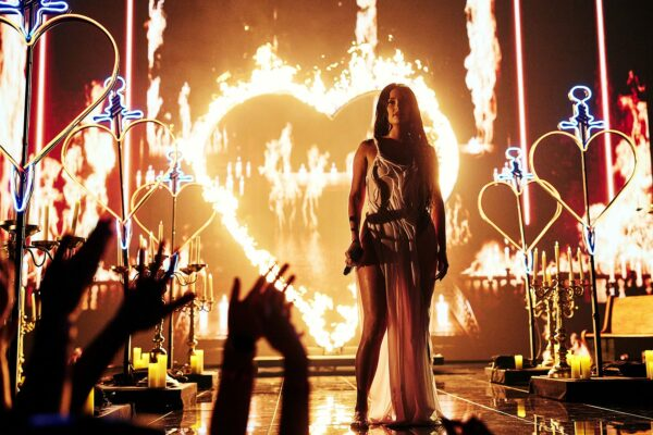 Kacey Musgraves is seen on stage surrounded by impressive pyrotechnics including neon heart shaped props and a heart on fire.