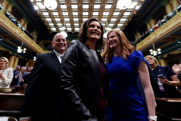 Gretchen Whitmer, Frank Liberati and Mallory McMorrow smile as people applaud.