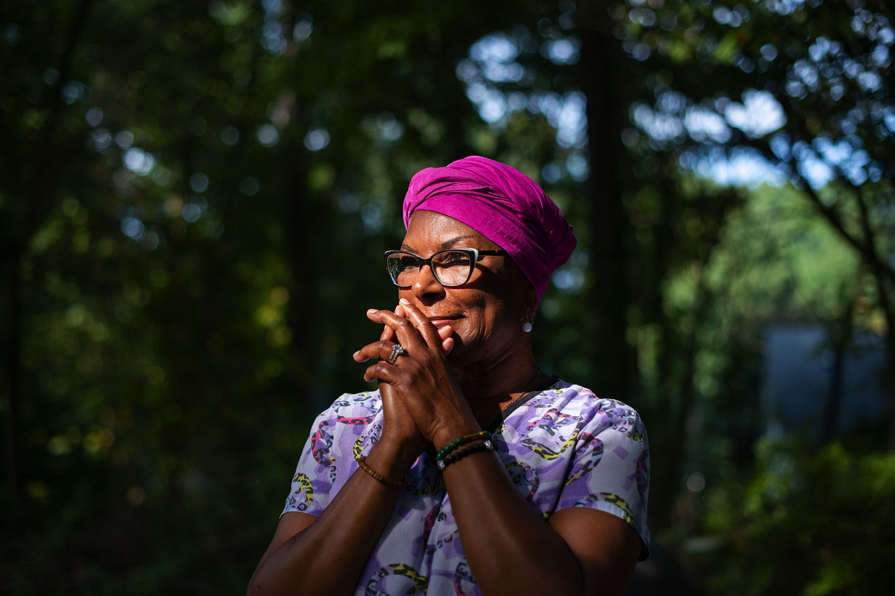 A woman wearing a pink turban and purple scrubs's face is lit by a ray of sun. She is surrounded by trees.