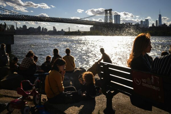 A woman accompanied by two children is on the phone as people sit near the East River. The manhattan skyline is seen in the background.