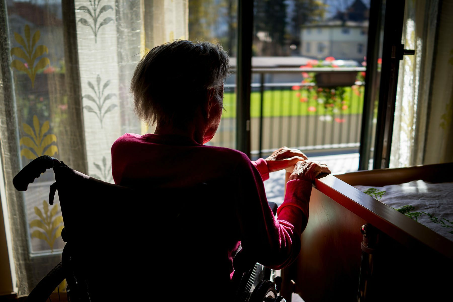 An older person in a wheelchair looks out a glass door. Their face is obscured while the sun shines on their hands.