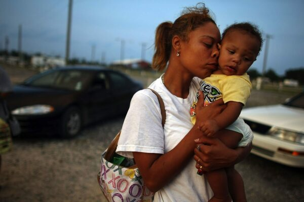 A young woman presses her face against a young child's face while standing on rubble road where cars are parked.
