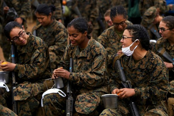 Female U.S. Marines eat oranges and speak to each other. They are wearing fatigues and holding rifles.