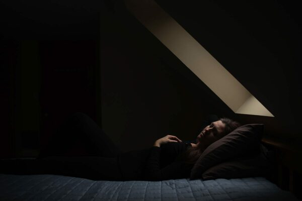 A woman lays on a bed as soft light trickles into the room from a skylight.