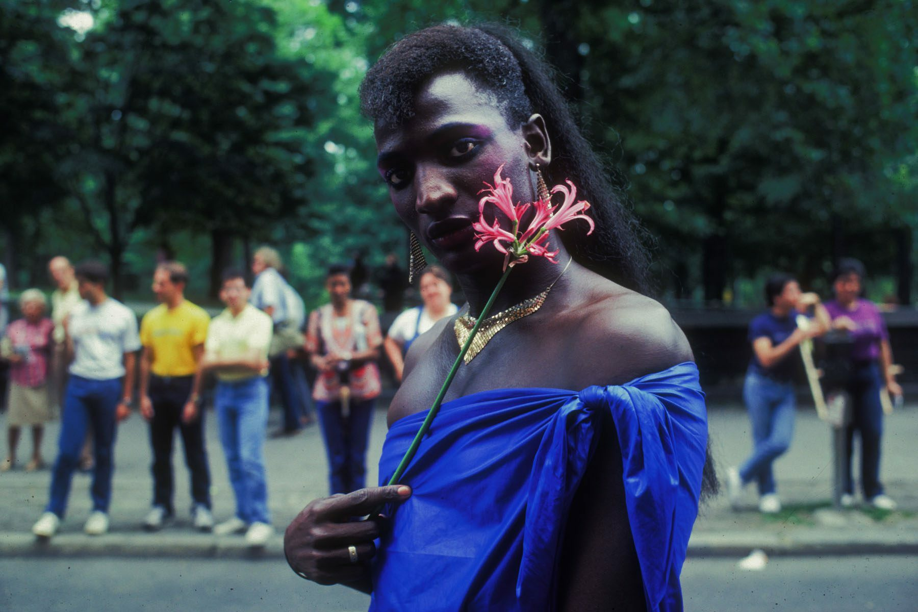 A participant wearing a golden necklace, earrings and a blue fabric as a top holds a flower to their cheek.