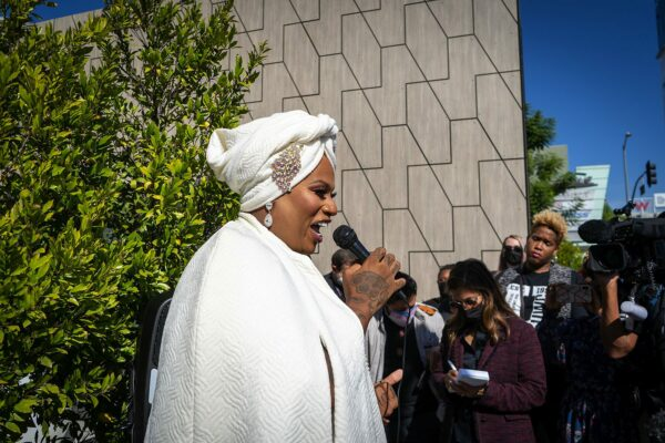 Ashlee Marie Preston dressed in a white cape and a white turban holds a microphone as people and press surround her.