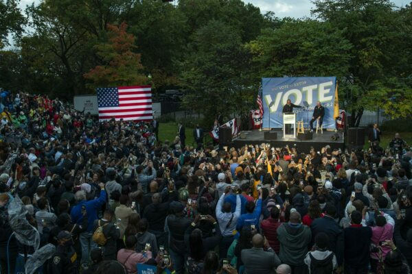 A crowd listens to former President Barack Obama as he campaigns for New Jersey Gov. Phil Murphy, with a vote sign behind him and an American flag to the side