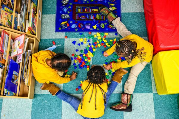 Three little girls seen from above play on a colorful classroom floor.