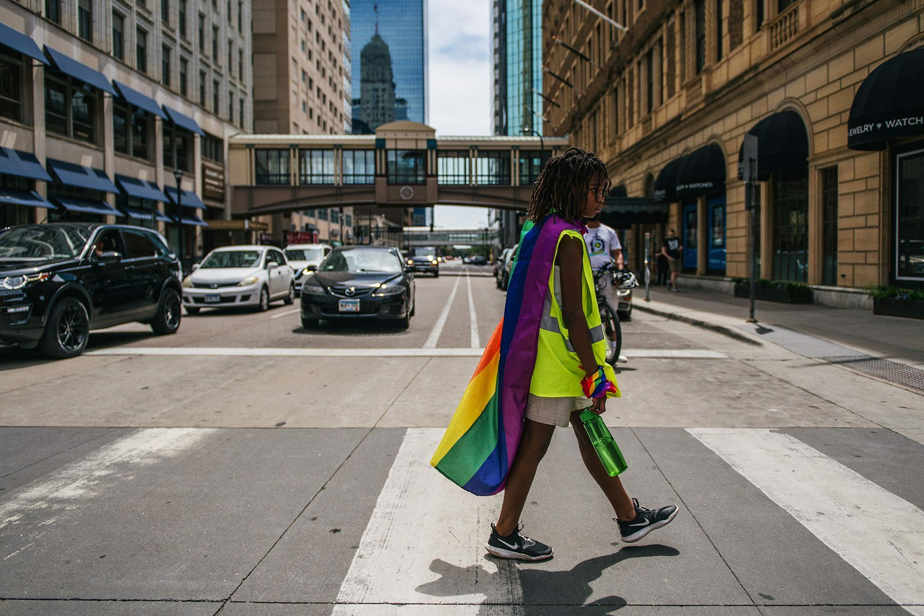 A young black child crosses the street wearing a pride flag around their shoulders and a pride bandana around their wrist.