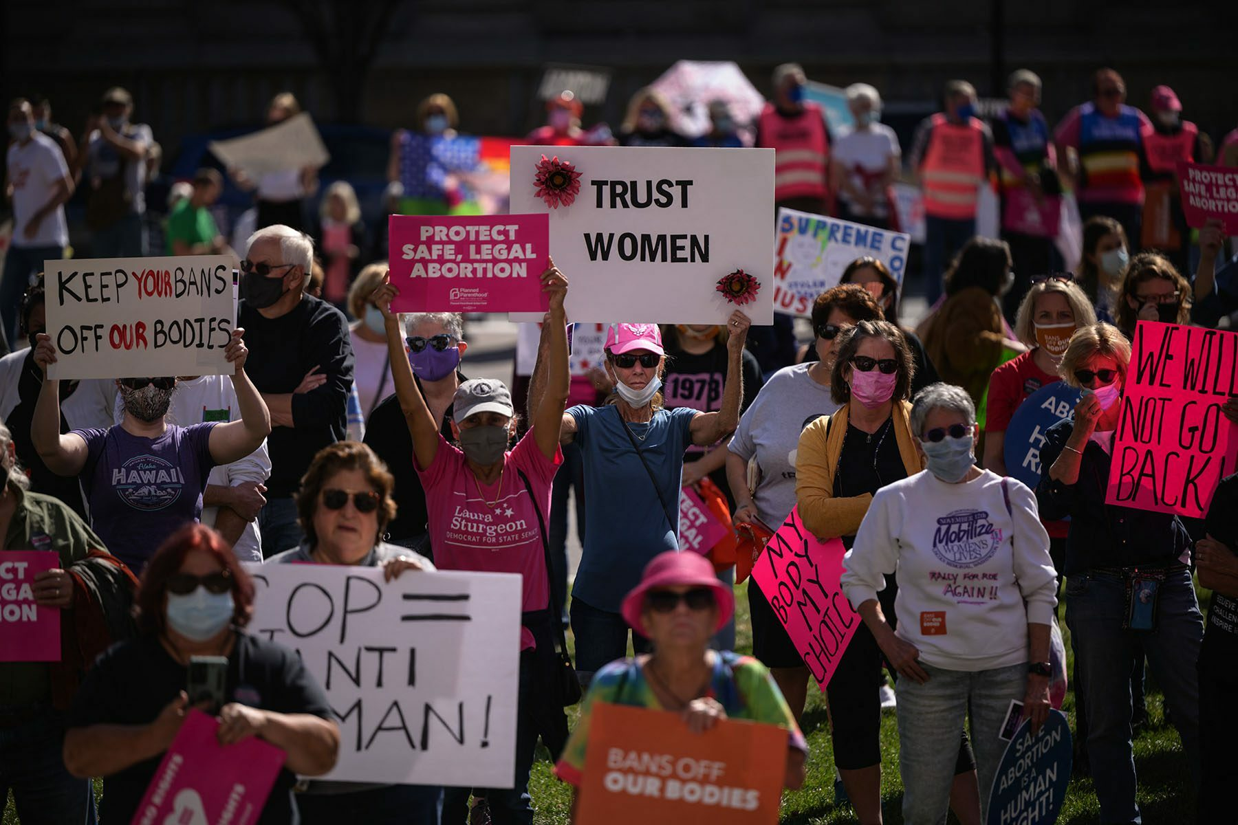 A crowd of abortion rights activists carry signs while demonstrating.