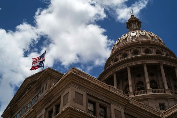 A U.S. and a Texas flag fly over the Texas State Capitol.
